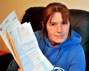Milton process worker Danelle Byrne holds several IRD letters demanding she file an overdue GST...