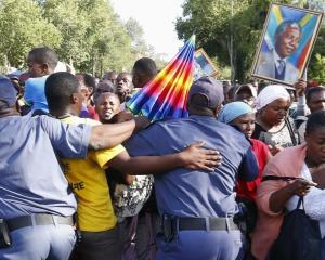 Mourners try to break through a police barrier attempt to view the body of former South African...