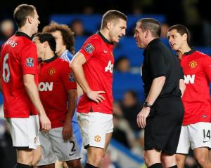 Nemanja Vidic (C) talks with referee Phil Dowd after being sent off. REUTERS/Stefan Wermuth