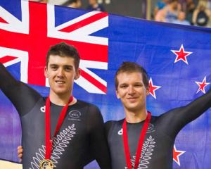 New Zealand cyclists Tom Scully, left, and Aaron Gate celebrate with their gold and bronze medals...