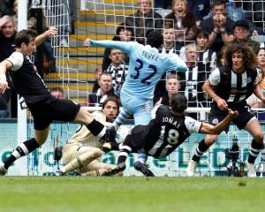 Newcastle United players tackle Manchester City's Carlos Tevez (C) as he tries to score during...
