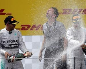 Nico Rosberg (R) and Lewis Hamilton splash each other with champagne after the Austrian Grand...