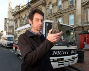 Night Bus Dunedin operator Andrew Rutherford with the rock he says was thrown through the window...