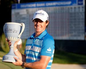 Northern Ireland golfer Rory McIlroy holds up the championship cup after winning the Deutsche...