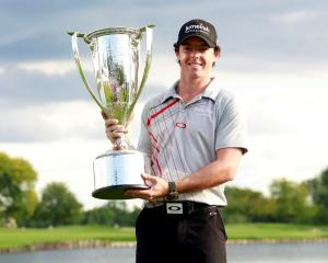 Northern Irish golfer Rory McIlroy poses with the champion's trophy after winning the PGA...