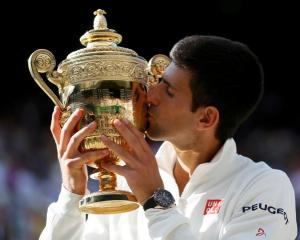 Novak Djokovic kisses the trophy after beating Roger Federer in their men's singles final at...
