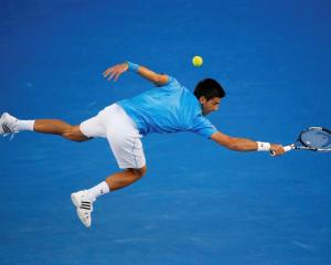Novak Djokovic lunges to hit a return against Milos Raonic during their men's singles...