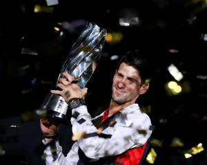 Novak Djokovic of Serbia celebrates with his trophy after winning the men's singles final against...