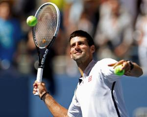 Novak Djokovic of Serbia hits balls to fans after defeating David Ferrer of Spain in their men's...