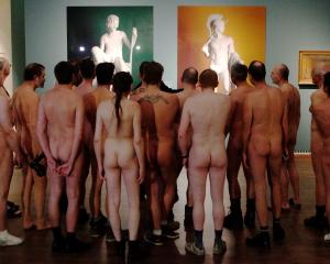 Nude visitors looks at the laserchrome prints 'Shepherd Boy' (L) and 'Jason' by Michael Elmgreen...