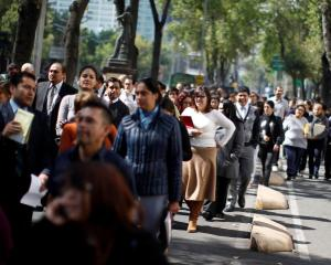 Office workers gather on Paseo de la Reforma avenue in Mexico City after being evacuated from the...