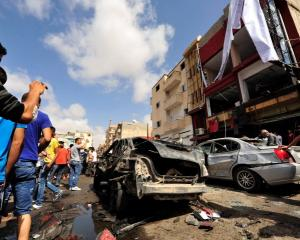 Onlookers take photographs following a car bomb explosion outside a hospital in Benghazi, Libya....