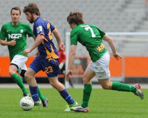 Otago United midfielder Regan Coldicott streaks past Manawatu defenders Grant Robson (left) and...
