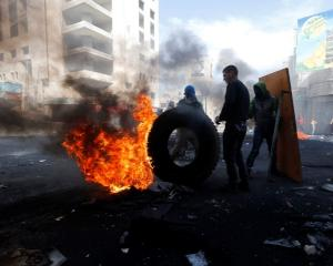 Palestinian protesters stand next to a burning tyre during clashes with Israeli troops in the...