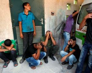 Palestinians mourn outside al-Aqsa hospital in Deir al-Balah in central Gaza Strip after an...