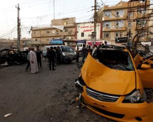 People gather at the site of a car bomb attack in Baghdad at the weekend. REUTERS/Thaier Al-Sudani