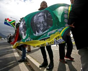 People hold a banner bearing the face of former South African president Nelson Mandela as they...