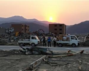 People stand among the rubble in the area devastated by the Match 11 earthquake and tsunami in...