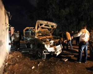 People stand near a police car that was destroyed in an explosion in front of a police station in...