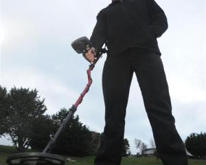Phil Wheeler uses a metal detector in his effort to locate a buried time capsule at his former...