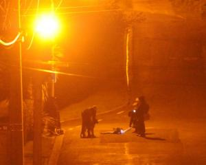 Police take a man into custody last night. Photo by Craig Baxter.