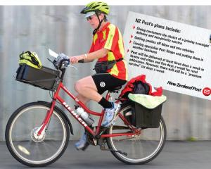 Postie Jane Gibbs heads down Ascot St in Dunedin yesterday. Photo by Peter McIntosh.
