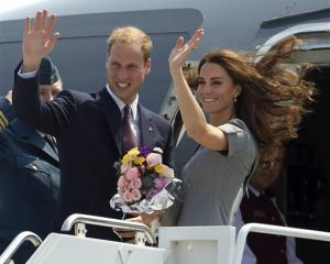 Prince William and Kate, the Duke and Duchess of Cambridge, wave as they board their plane as...