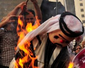 Protesters burn an effigy of Qatar's Emir Sheikh Hamad bin Khalifa al-Thaniat during a...