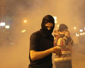 Protesters opposing Egyptian President Mohamed Mursi and the Muslim Brotherhood run from tear gas...