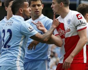 Queens Park Rangers' Joey Barton (R) confronts Manchester City's Carlos Tevez during their...