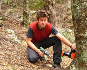 Queenstown Climbing Club committee member Philip Green installs a possum trap at Wye Creek, south...