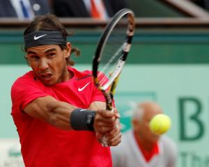 Rafael Nadal of Spain returns the ball to Novak Djokovic of Serbia during their singles final at...