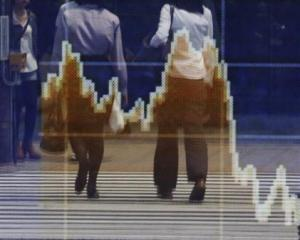 Reflections in a stock quotation board showing the falling Topix index outside a brokerage in...