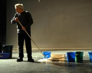 Regent Theatre technical manager Nelson Miles mops the floor after water cascaded on to the stage...
