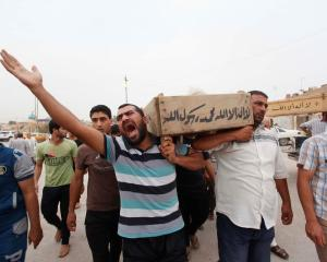 Relatives carry the coffin of an Iraqi police officer killed by militants, during a funeral in...