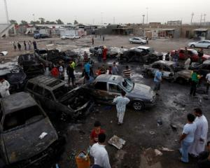 Residents gather at the site of a car bomb attack in Baghdad's Sadr City. REUTERS/Thaier al-Sudani