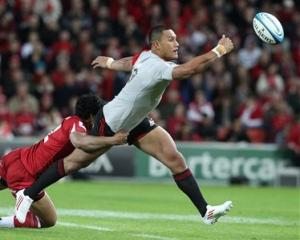 Robbie Fruean of the Crusaders, right, is tackled by Ben Tapuai of the Reds. (AP Photo/Tertius...