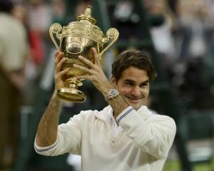 Roger Federer of Switzerland holds the winners trophy after defeating Andy Murray of Britain in...