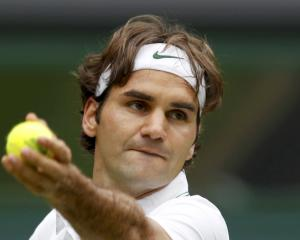 Roger Federer of Switzerland serves to Fabio Fognini of Italy during their men's singles match at...