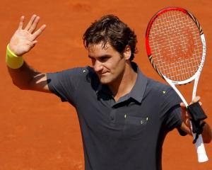Roger Federer of Switzerland waves after winning his match against Tobias Kamke of Germany at the...