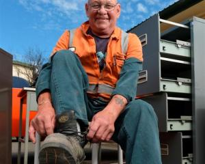 Roger Parsons removes his work boots for the last time yesterday,  signalling his retirement...