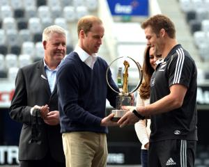 Prince William presents the IRB World Trophy to McCaw while watched by NZ Rugby chief executive...