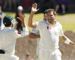 Ryan Harris (R) of Australia celebrates with Ed Cowan (L) after taking the wicket of Ishant...