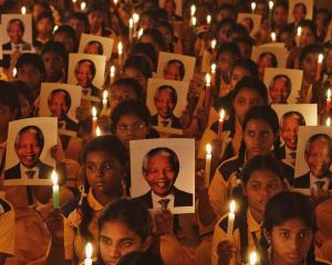 Schoolchildren hold candles and portraits of Nelson Mandela during a prayer ceremony at a school...