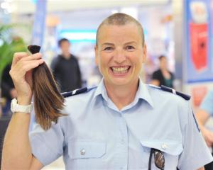 Senior Constable Helen Fincham-Putter gets her head shaved by hairdresser Jordan Hill at the...