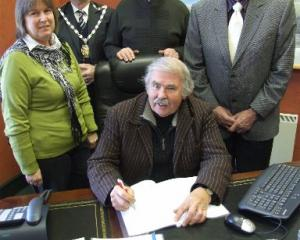 Signing a trust deed this week are Hearts and Hands for Haiti trustees Bruce Albiston (seated,...