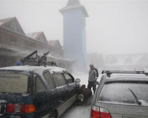 Skiers at Cardrona Ski Area  fit chains to their vehicles for the journey down the mountain as a...