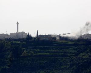 Smoke rises after shells exploded in the Syrian village of al-Jamlah, close to the ceasefire line...