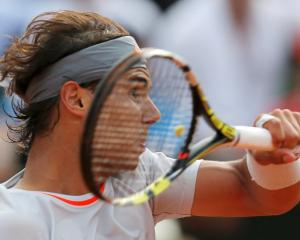 Spain's Rafael Nadal hits a return to Stanislas Wawrinka of Switzerland during their men's...