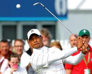 Spectators watch as US golfer Tiger Woods hits shots during a practice round ahead of the British...